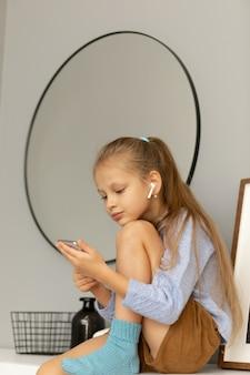 Chica mirando el teléfono y viendo una película o usando aplicaciones móviles.