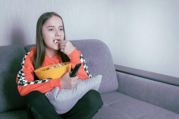 Chica mirando televisión, sentada con el control remoto en el sofá, comiendo palomitas de maíz