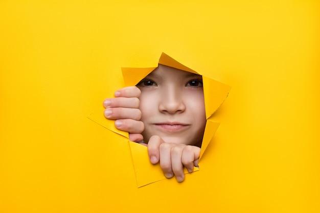 Chica mirando a través de un agujero en papel de color