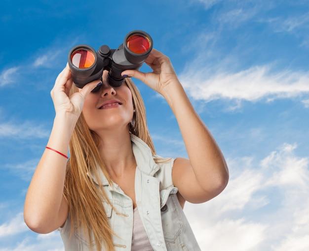 Chica mirando a través de prismáticos el cielo