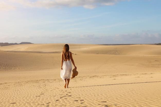 Chica misteriosa con vestido blanco y sombrero caminando sobre la arena dorada de las dunas del desierto al atardecer