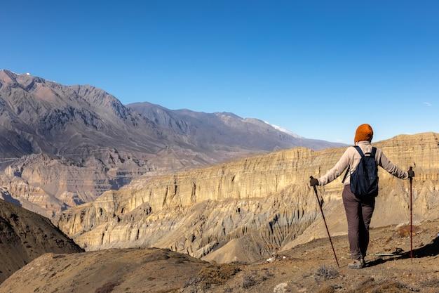 Chica con una mochila y bastones de trekking mirando montañas.