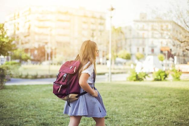Chica con mochila caminando por el césped en la ciudad
