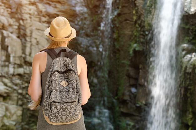 Chica con mochila y sombrero mirando una cascada. vista desde atrás