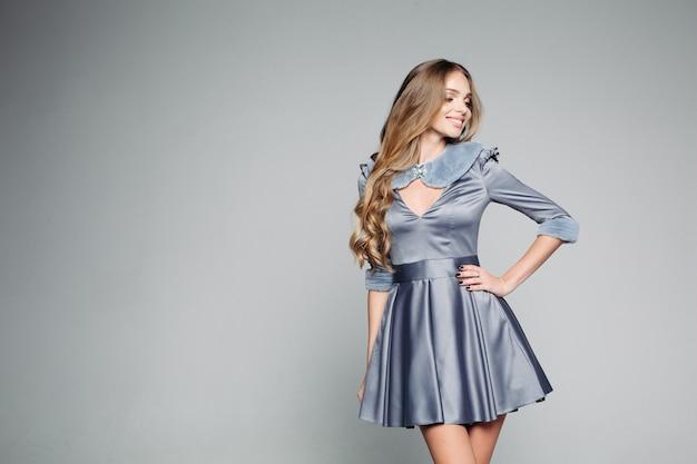 Chica de moda blondie en vestido gris dtylish posando en estudio.