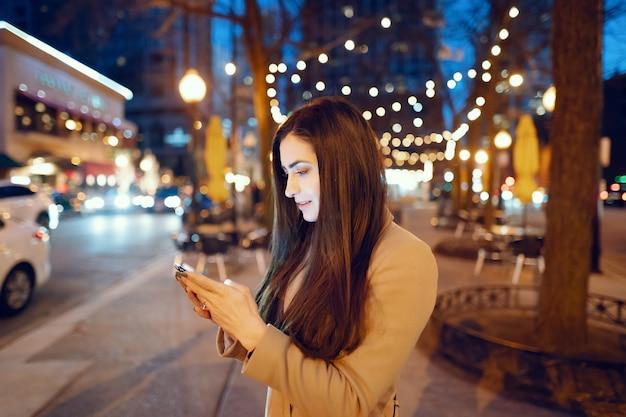 Chica de moda caminando en una ciudad de noche