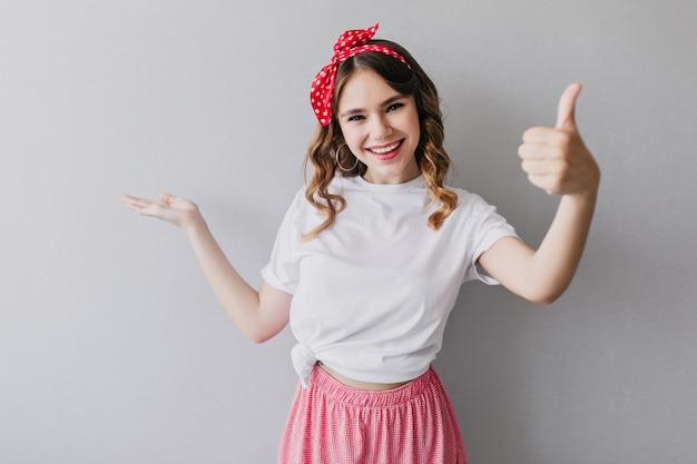 Chica de moda con cinta roja sonriendo con el pulgar hacia arriba. retrato de dama fascinante en ropa de verano de moda.
