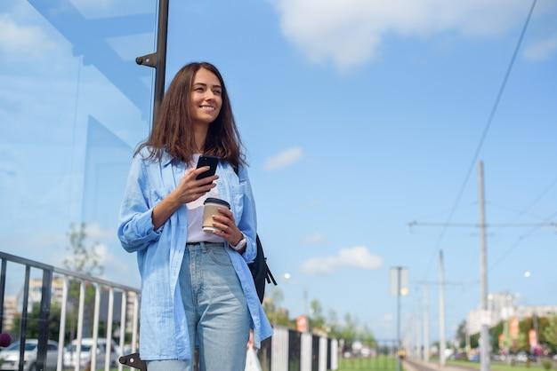 Chica de moda espera el autobús o el tranvía en la estación de transporte público en la mañana. mujer joven con taza de café y teléfono inteligente monitoreo de transporte a través de la aplicación.