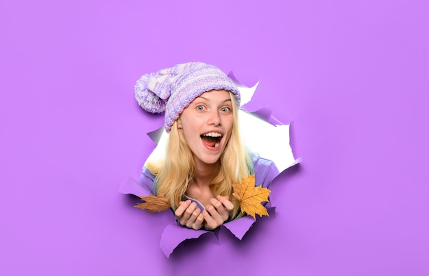 Chica de moda de estilo de belleza mira a través de papel rasgado con hojas de otoño tendencia de moda casual para el otoño