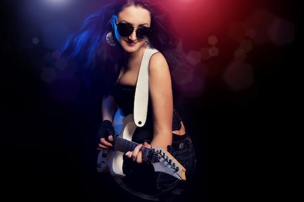 Chica de moda con guitarra tocando hard rock
