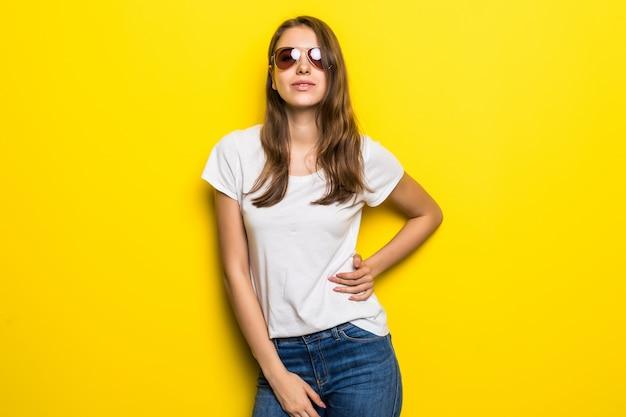 Chica de moda joven en camiseta blanca y pantalones de mezclilla permanecer delante de fondo de estudio amarillo