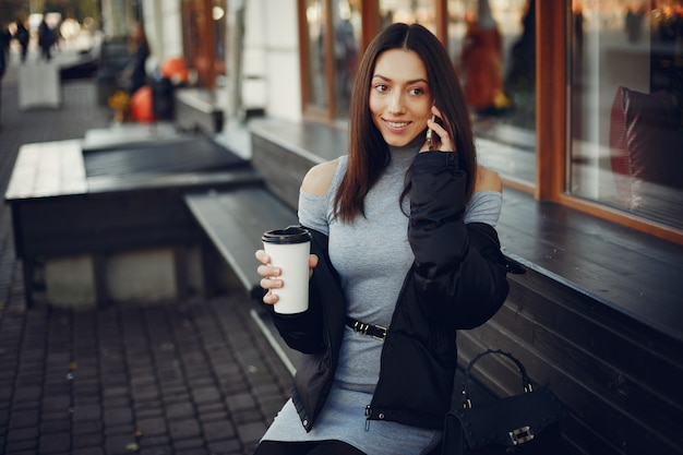 Chica de moda sentada en una ciudad de verano