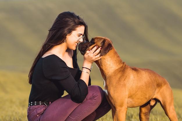 Chica de moda con su perro boxer en el prado en otoño