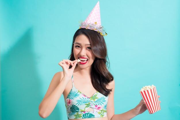 Chica de moda de verano en traje de verano comiendo palomitas de maíz.