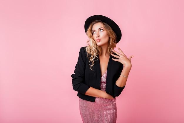Chica de moda en vestido de fiesta rosa con lentejuelas posando en la pared de color rosa. traje elegante alto look de moda.