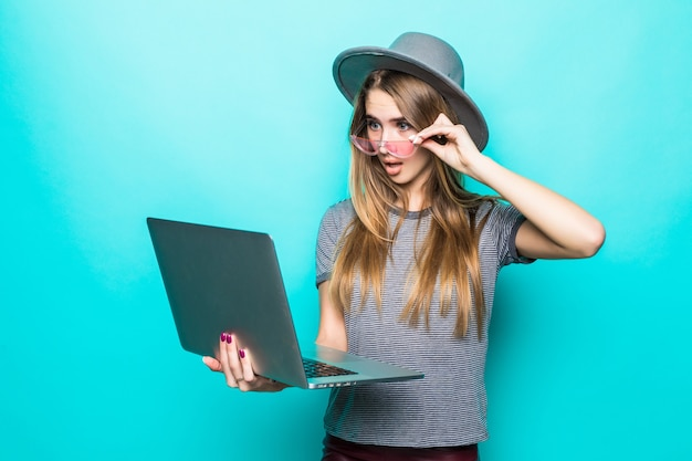 Chica modelo de estudiante avergonzado en ropa casual de moda trabaja relojes en su computadora portátil aislada en verde