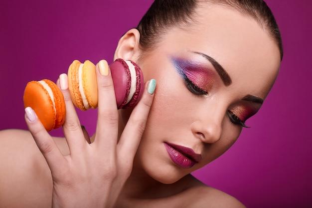 Chica de modelo de moda de glamour de belleza con maquillaje colorido y macarrones.