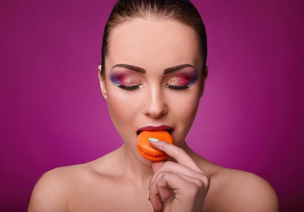 Chica de modelo de moda de glamour de belleza con maquillaje colorido y macarrones