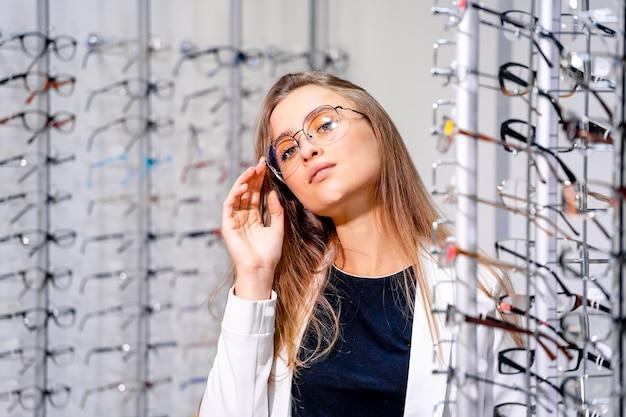 Chica modelo está de pie con un juego de gafas en una tienda óptica