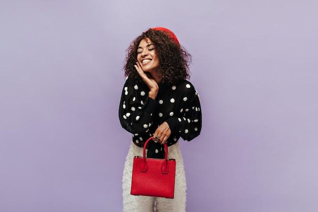 Chica moderna alegre con peinado ondulado y gorra fresca en blusa negra de lunares sonriendo y sosteniendo un elegante bolso rojo en la pared lila
