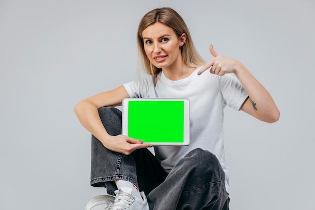 Chica moderna en camiseta blanca con tableta en estudio creatividad libre