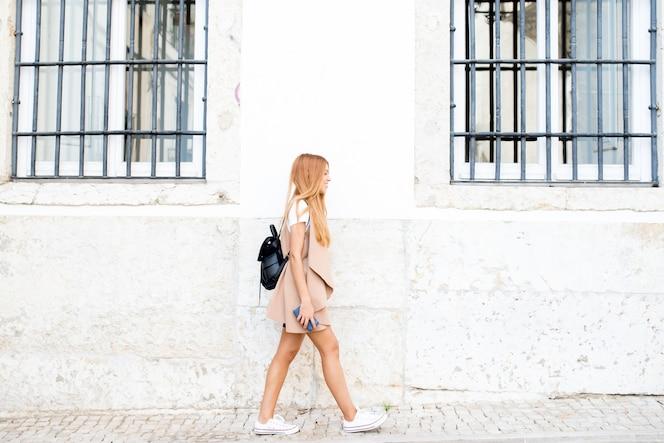 Chica moderna hipster moviéndose a lo largo de la calle de la ciudad