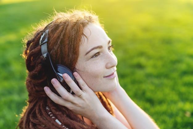 Chica moderna con rastas escuchando música con sus auriculares en otoño sunny park