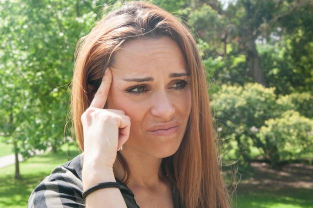 Chica molesta que sufre de dolor de cabeza o mala vista