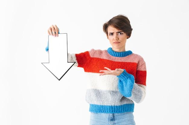 Chica molesta vistiendo suéter de pie aislado en blanco, apuntando hacia abajo con una flecha de papel