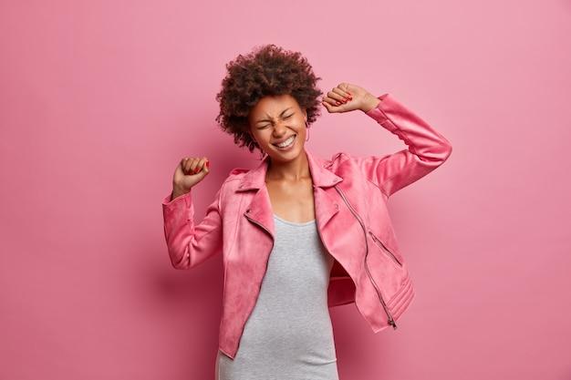La chica sin molestias se divierte y baila sin preocupaciones, hace un movimiento de discoteca genial, levanta las manos, cierra los ojos y sonríe ampliamente, vestida con una chaqueta a la moda