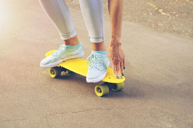 Chica monta en la carretera en un monopatín de plástico en la luz del sol