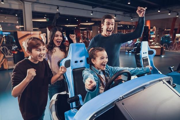 La chica está montando un auto en un arcade. la familia está animando y ayudando.