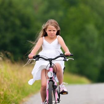 Chica montando una bicicleta en verano