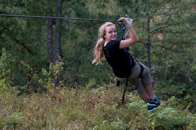 Chica montando una tirolina en un bosque, copán, copán ruinas, departamento de copán, honduras