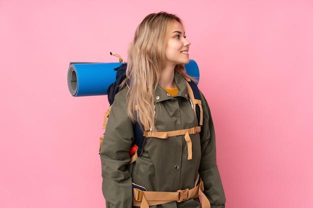 Chica montañista adolescente con una mochila grande aislada en el lado de aspecto rosa
