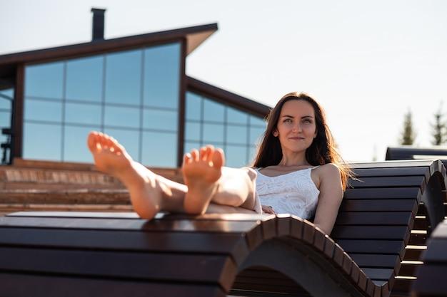 Chica morena acostada en una tumbona de madera descalzo y sonriente