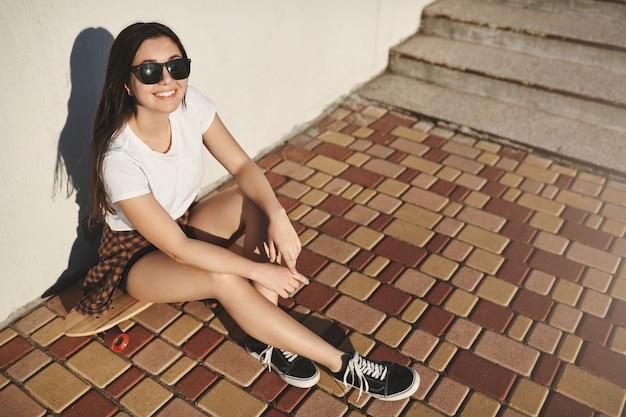 Chica morena alegre y despreocupada en traje de hipster, patinador