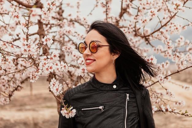 Chica morena atractiva cerca de un almendro con muchas flores