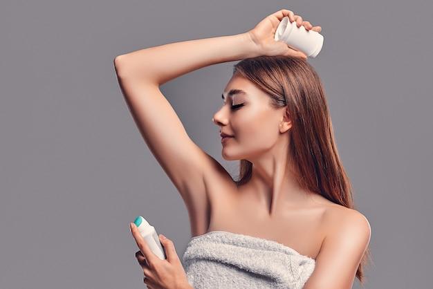 Chica morena atractiva joven con el pelo suelto con desodorante en barra y aerosol antitranspirante aislado sobre fondo gris. cuidado del cuerpo.