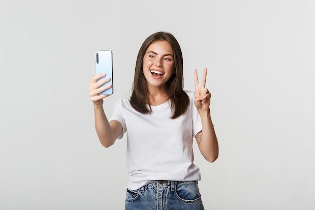 Chica morena atractiva mirando feliz y tomando selfie en smartphone