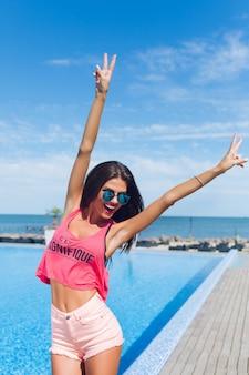 Chica morena atractiva con el pelo largo está posando para la cámara junto a la piscina. ella muestra emociones felices.