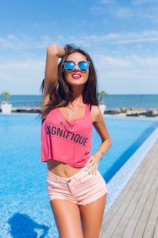 Chica morena atractiva con el pelo largo está posando para la cámara junto a la piscina. ella sonríe a la cámara.