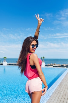 Chica morena atractiva con el pelo largo está posando para la cámara junto a la piscina. ella sostiene la mano arriba y se ve feliz y feliz.
