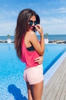 Chica morena atractiva con el pelo largo está posando para la cámara junto a la piscina. ella sostiene la mano cerca de la cara y sonríe.
