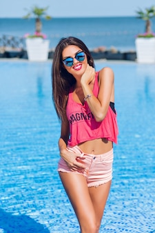 Chica morena atractiva con el pelo largo está posando para la cámara junto a la piscina. ella tiene las manos en el cuerpo y sonriendo a la cámara.