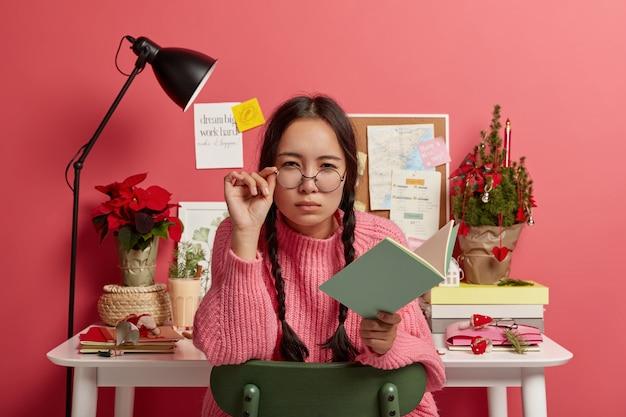 Chica morena atractiva seria mira sospechosamente a través de gafas redondas, mantiene la mano en el marco, sostiene el bloc de notas abierto o el diario