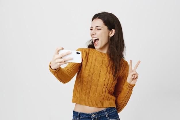 Chica morena atractiva tomando selfie en smartphone