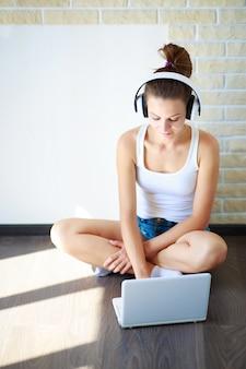 Chica morena con auriculares escuchando música en una computadora portátil en una habitación vacía