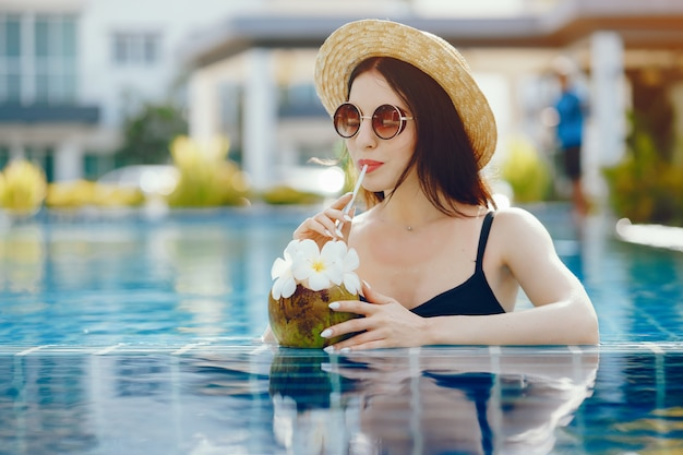 Chica morena bebiendo jugo de coco en la piscina