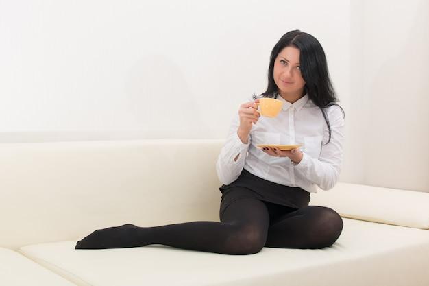 Chica morena en una blusa blanca se sienta en un sofá con una taza de café